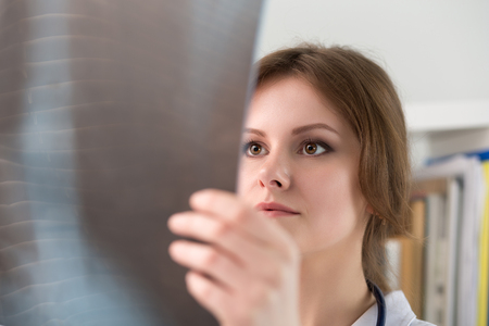 Young female doctor looking at lungs x-ray image. Healthcare and medical concept