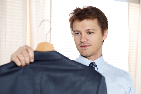 workday: Business man holding his coat and looking at it ready to put it on. Preparing for some event or new workday. New opportunities, dating, wedding day, shopping or laundry service concept. Focus on hand