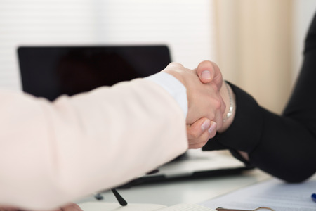 handclasp: Two women handshake in office closeup. Businesswomen shaking hands. Serious business, partnership and collaboration concept. Partners made deal and sealed it with handclasp. Formal greeting gesture