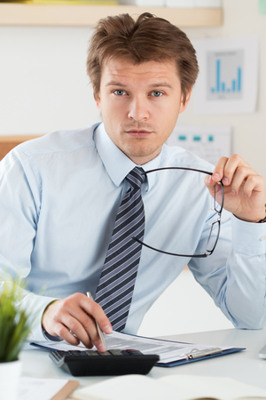 home inspector: Portrait of bookkeeper or financial inspector holding his glasses making report, calculating or checking balance. Home finances, investment, economy, saving money or insurance concept Stock Photo