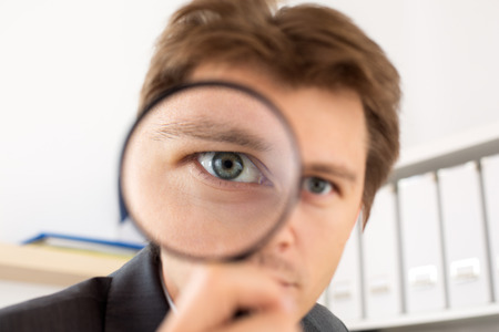 find a job: Funny business man holding magnifying glass portrait. Private detective investigation, layer, crime, business research or security concept