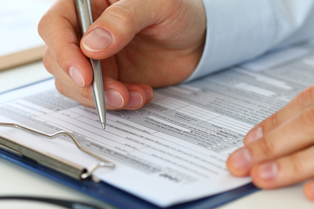 home finances: Close up of male accountant filling tax form. Man writing something sitting at his office. Filling individual income tax return form 1040, making financial report, home finances or economy concept