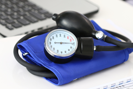 preventive: Close up view of manometer laying on working table near laptop. Hospital workspace. Healthcare, medical service, treatment, hypotonia or hypertension concept.
