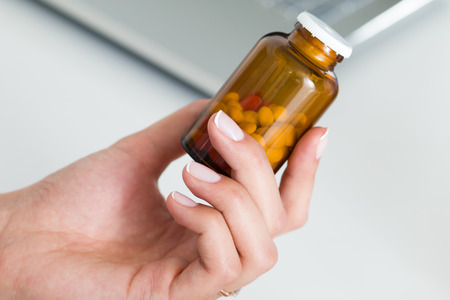 hand holding bottle: Close up view of female doctor hand holding bottle with pills and writing prescription. Healthcare, medical and pharmacy concept.