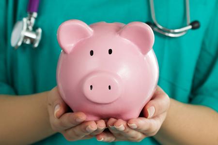 Vrouwelijke geneeskunde arts draagt ??groene uniform bedrijf grappig roze spaarvarken. Doctor handen close-up. Medische dienst economie, besparingen gezondheidszorg en verzekeringen concept. Focus op spaarvarken Stockfoto - 60087333