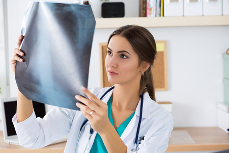 x ray image: Young female medical doctor or intern looking at lungs x ray image standing at her office. Radiology, healthcare, medical service or education concept.