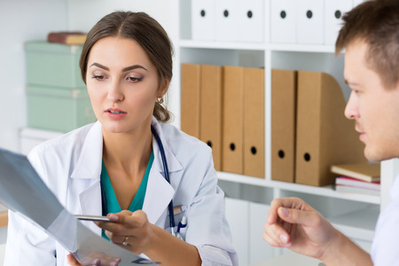 disease prevention: Female doctor showing something to her male colleague or patient. Physical exam, er, disease prevention, ward round, visit check, 911, prescribe remedy, healthy lifestyle concept