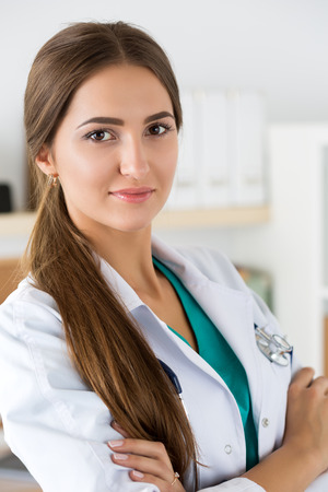 Portrait of female medicine therapeutist doctor standing with hands crossed on her chest wearing stethoscope in office. Medical help or insurance concept. Physician is waiting for patient to examine photo