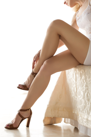 Beautiful woman sitting on bed and touching her leg. Beautiful slender legs closeup. Stock Photo