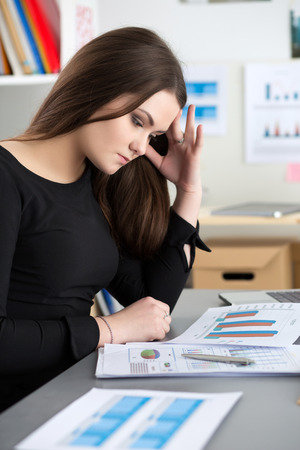 distress: Tired female employee at workplace in office touching her head trying to concentrate. Sleepy worker early in the morning. Overworking, making mistake, stress, termination or depression concept