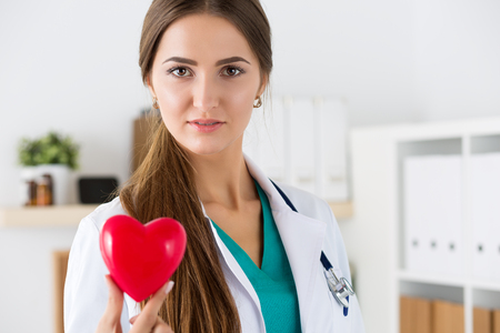 Female medicine doctor hold in hands red toy heart closeup. Cardio therapeutist, physician make cardiac physical, heart rate measure or arrhythmia concept