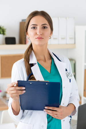 Portrait of female medicine therapeutist doctor in white coat holding clipboard in office. Medical help or insurance concept. Physician is waiting for patient to examine photo