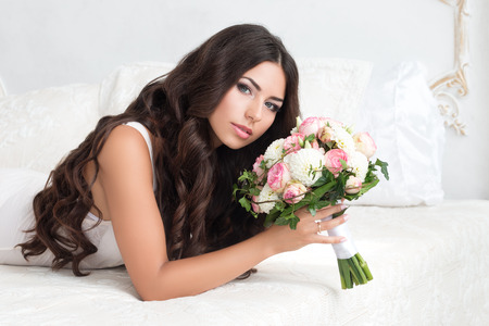 nuptial: Beautiful bride in white lingerie holding nuptial bouquet laying on bed