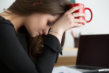 Tired female employee at workplace in office holding red cup and touching her head. Sleepy worker early in the morning. Overworking, making mistake, stress, termination or depression concept