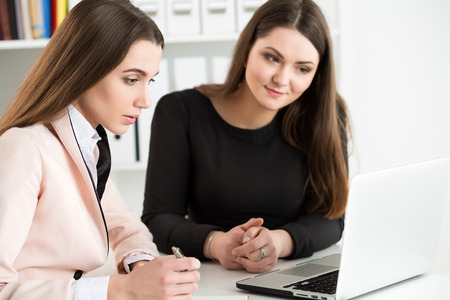 coursework: Two woman sitting at office and looking at laptop monitor discussing some questions. E-business, distant education or business meeting concept