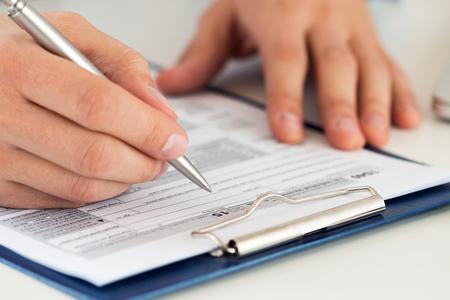 Gros plan de la forme d'impôt mâle de remplissage comptable. écrire quelque chose l'homme assis à son bureau. Remplir la déclaration de revenus sous forme individuelle 1040, ce qui rend le rapport financier, les finances de la maison ou concept d'économie Banque d'images - 60087405