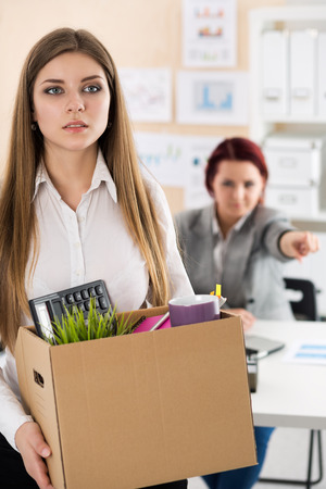 dismissed: Boss dismissing an employee. Dejected fired office worker carrying a box full of her belongings. Getting fired concept. Stock Photo