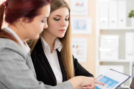 Two woman sitting at office and looking at charts and tables discussing some questions. Financial planning, accounting, irs, presentation or business meeting concept