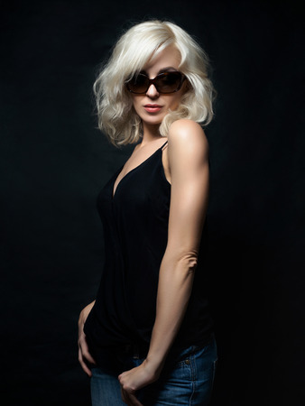 donne mature sexy: Beautiful blonde woman wearing sunglasses posing over black background. Model tests. Fun fashion studio shot