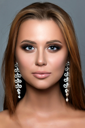portrait studio: Close up portrait of young woman with bronze smokey eyes wearing long earrings. Modern bridal make-up. Perfect brows. Studio shot