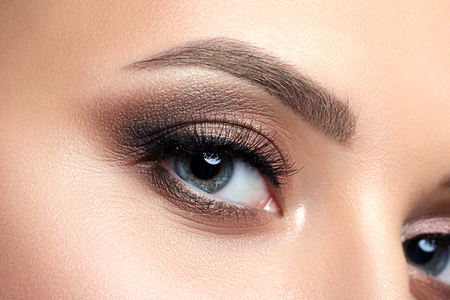luxury liner: Close up view of blue woman eye with beautiful golden shades and black eyeliner makeup. Classic make up. Perfect brows. Studio shot Stock Photo