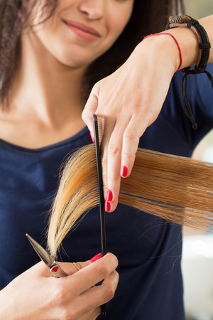 shorten: Close up view of female hairdresser hands cutting hair tips. Keratin restoration, healthy hair, latest hair fashion trends, changing haircut style, shorten split ends, instrument store concept