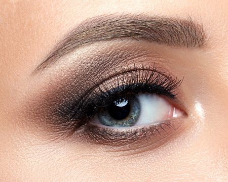 maquillaje de ojos: Cierre de vista de ojo azul mujer con bellos tonos dorados y maquillaje delineador de ojos negro. Clásico maquillaje. cejas perfectas. tiro del estudio Foto de archivo