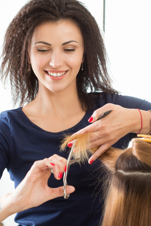 shorten: Smiling female hairdresser cutting client hair tips. Keratin restoration, healthy hair, latest hair fashion trends, changing haircut style, shorten split ends, instrument store concept