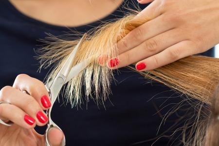 Close-up van vrouwelijke kapper handen snijden haar tips. Keratine restauratie, gezond haar, nieuwste haarmode trends, veranderende kapsel stijl, verkorten gespleten haarpunten, concept instrument store