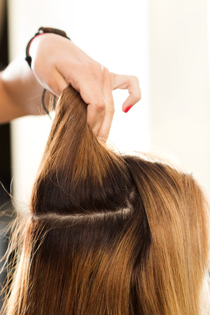 haircutting: Close up view of hairdresser hand holding strand of hair preparing to cutting and dyeing hair. Haircare, making new hairdo, keratin restoration and hair therapy concept