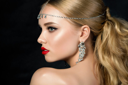 luxury liner: Portrait of young beautiful woman with evening make up looking over her shoulder. Model posing over dark background. Red lips and eyeliner. Classic makeup concept. Studio shot.