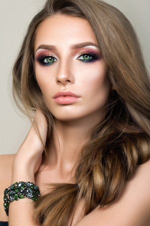 Beauty portrait of young pretty girl with green eyes wearing green bracelet and touching her hair. Modern smokey eyes make up. Studio shot.