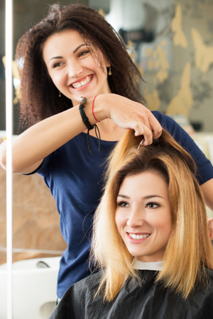 Female hairdresser and client deciding what haircut to do. Healthy hair, latest hair fashion trends, changing haircut style concept