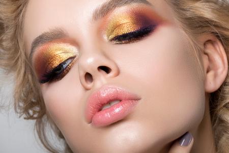 Bliska portret piękna młoda kobieta z pięknym letnim jasnym makijażu. Nowoczesne smokey eyes z kolorowych cieni metalicznych. studio strzał