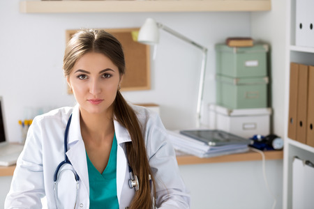Portrait of female medicine therapeutist doctor sitting at her office. Medical help or insurance concept. Physician is waiting for patient to examine photo