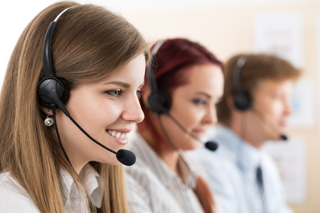 handsfree telephone: Portrait of call center worker accompanied by her team. Smiling customer support operator at work. Help and support concept