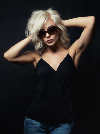 Beautiful blonde woman wearing sunglasses posing over black background. Model tests. Fun fashion studio shot