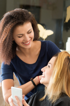 Smiling hairdresser looking on client showing on mobile phone what haircut she wants to do. Healthy hair, latest hair fashion trends, changing haircut style concept