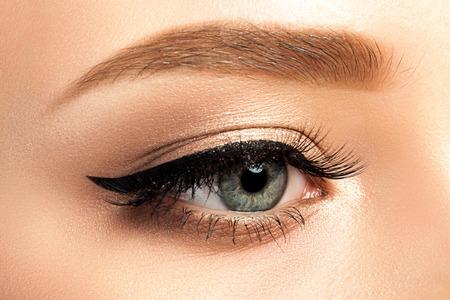 Nahaufnahme des grauen Frauenauges mit schönen goldenen Schattierungen und schwarzem Eyeliner-Make-up. Klassisches Make-up. Studioaufnahme