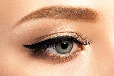 Close up view of gray woman eye with beautiful golden shades and black eyeliner makeup. Classic make up. Studio shot