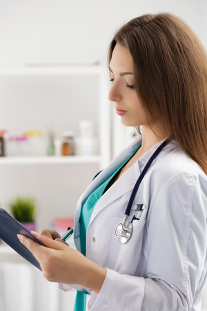 Female medicine doctor filling in patient medical history list during ward round. Medical care or insurance concept. Physician ready to examine patient and help. Stock Photo