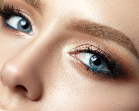 Close up view of blue woman eye with beautiful golden shades and black eyeliner makeup. Classic make up. Perfect brows. Studio shot Stock Photo