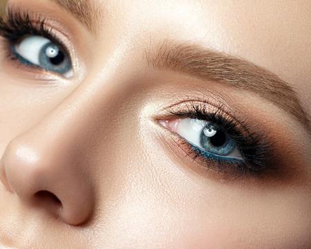 Close up vista della donna occhio blu con belle sfumature dorate e trucco eyeliner nero. Classic make up. sopracciglia perfette. Lo studio ha sparato