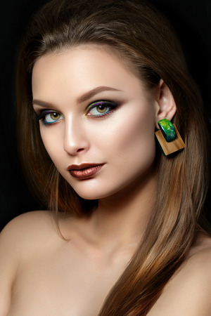 ojos verdes: Cerca de retrato de mujer joven con los labios marrones y ahumados ojos verdes sobre fondo negro. Las cejas perfectas. moda moderna componen. tiro del estudio