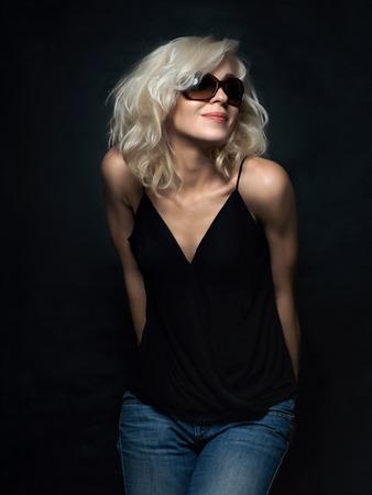 Beautiful blonde woman wearing sunglasses posing over black background. Model tests. Fun fashion studio shot