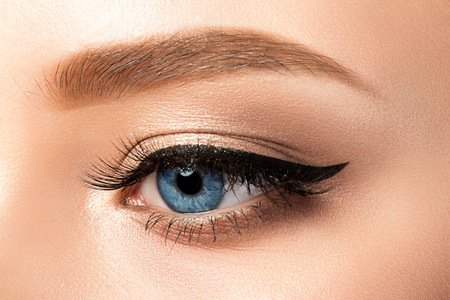 Close up view of blue woman eye with beautiful golden shades and black eyeliner makeup. Classic make up. Studio shot 免版税图像
