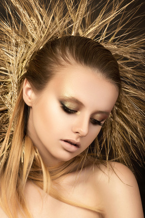 Portrait of young beautiful blonde girl with golden ears wreath. Autumn and yield concept. Modern make up. Studio shot