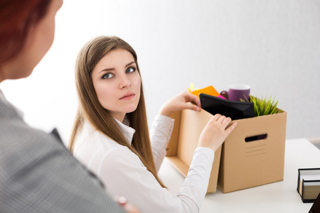 dejected: Boss dismissing an employee. Dejected fired office worker looking at her boss and packs her belongings to carton box. Getting fired concept. Stock Photo