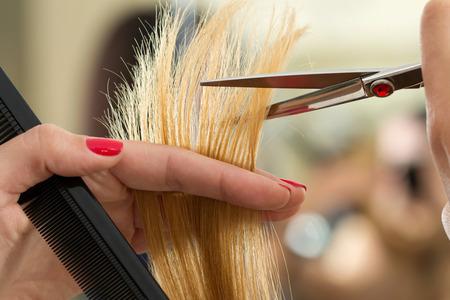 Close-up van vrouwelijke kapper handen snijden haar tips. Keratine restauratie, gezond haar, nieuwste haarmode trends, veranderende kapsel stijl, verkorten gespleten haarpunten, concept instrument store Stockfoto - 66205377
