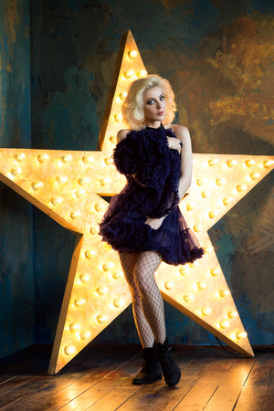 glowing star: Beautiful playful adult blonde woman wearing dark blue lace tutu skirt and mesh stockings posing over dark background with glowing star. Actress playing on stage. Theatre or dancer.